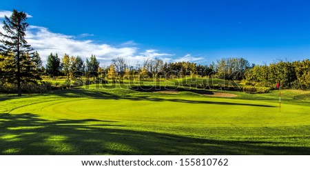 The fall colors of autumn surround the greens of the golf course - stock photo