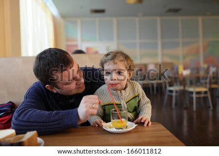 The family drinking juice in a restaurant - stock photo