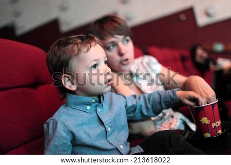 The family eating popcorn in the cinema - stock photo