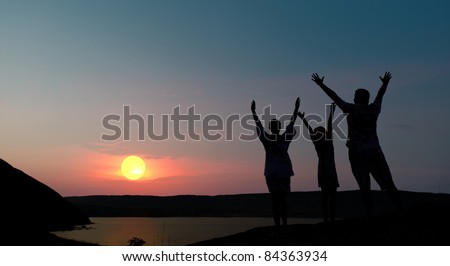 The family from three persons welcomes the sunset sun. - stock photo