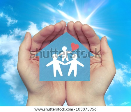 The family in the house. Hands holding a house with a happy family against the backdrop of the sunny sky. - stock photo