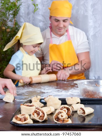 The family makes cakes with raisins, a focus on pastry - stock photo
