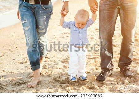The family of a man a woman and child walking on the beach and breathe the sea air - stock photo