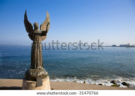 The famous Angel of Hope and Messenger of Peace statute in Puerto Vallarta Mexico created by artist Hector Manuel Montes Garcia, greets visitors to the Malecon. - stock photo