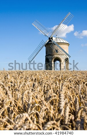 The famous listed windmill at Chesterton in Warwickshire, England, on a sunny summer afternoon. Focus on windmill with short depth of field. Wheat field in foreground with blue skies overhead. - stock photo
