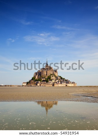 the famous Mont-St-michel on a summer morning at ebb tide, partially reflected in the water - stock photo