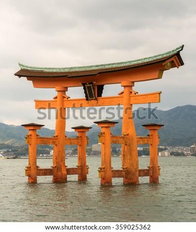 The famous orange floating shinto gate (Torii) of Itsukushima shrine panorama, Miyajima island of Hiroshima prefecture, Japan under Dramatic Cloud Sky - stock photo