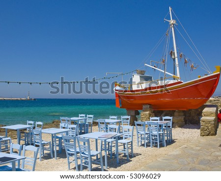 The famous red boat and a tavern on the island of Mykonos - stock photo