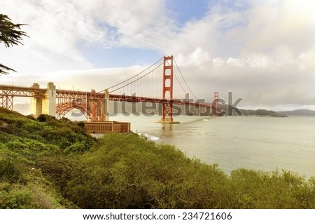 The famous San Francisco Golden Gate Bridge in California, United States of America. A view of Fort Point, the bay, surfers and the red suspended bridge connecting Frisco to Marin County at sunset. - stock photo