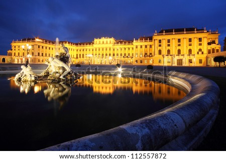 The famous Schonbrunn Palace in Vienna, Austria, with its beautiful water fountains in front, by twilight. - stock photo