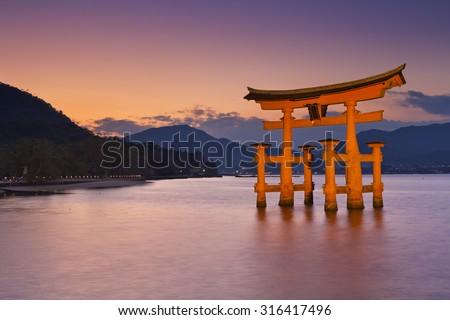The famous torii gate of the Itsukushima Shrine on Miyajima. Photographed at sunset. - stock photo