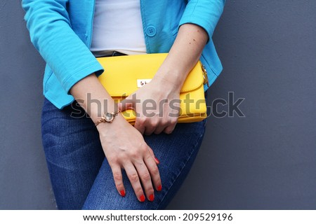 The fashionable young woman  holding yellow handbag clutch gray background - stock photo