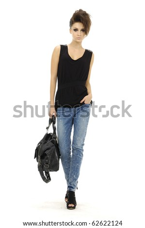 The fashionable young woman in blue jeans show in studio - stock photo