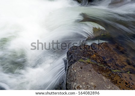 The fast waters of a clear river in Montana. - stock photo