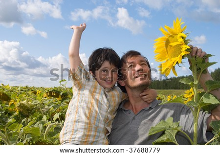 The father and boy  with sunflower and bottle of oil on field - stock photo