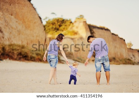 the father and mother hold the daughter by a hand, a young family on holiday