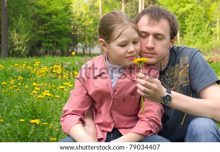 The father and the daughter on a green meadow with dandelions - stock photo