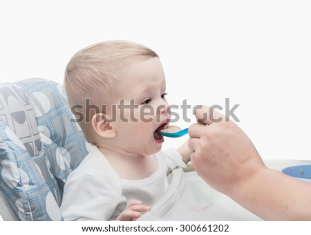 The father feeds with porridge of the one-year-old kid,  isolated on white background - stock photo