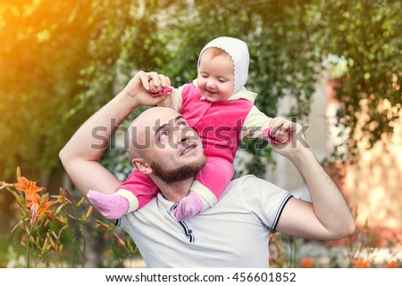 The father holds his daughter on his hands, standing in the bushes, kissing sown play a warm summer day nature Park