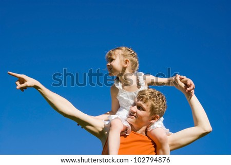 The father holds the daughter on his shoulders, and indicates - stock photo