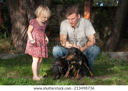 The father in a light shirt on a lawn shows to the fair-haired daughter of two quiet dogs - stock photo