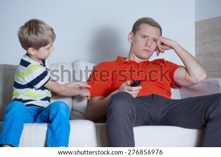 The father is not interested in his son at home - stock photo