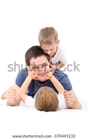 The father playing with sons lying isolated on white background - stock photo