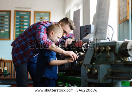 The father teaches his son work on the machine - stock photo