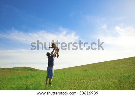 The father with a daughter jump on a green meadow