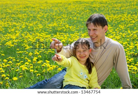 The father with a daughter sit on a lawn and show in a distance