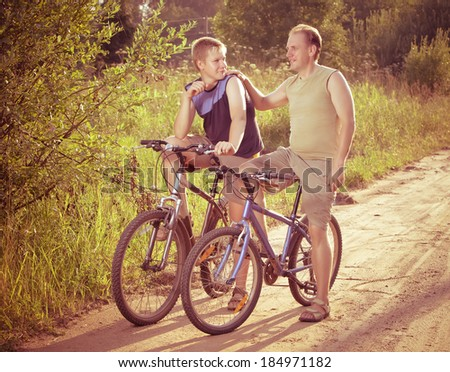 The father with the son on bicycles,with a retro effect - stock photo