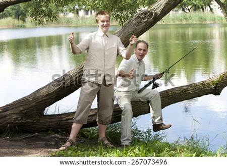 The father with the son on fishing, shows the size of fish - stock photo