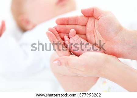 the feet newborn baby in arms him mother - stock photo