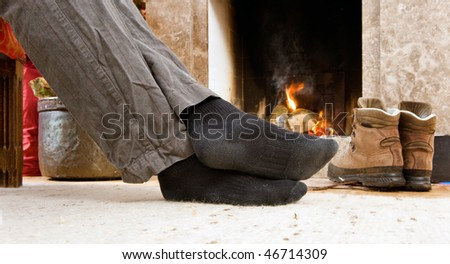 The feet of a hiker warming up by the fire