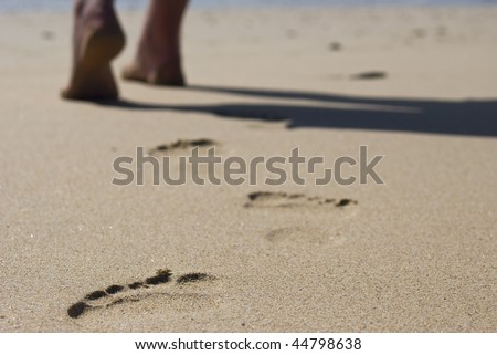The feet of a lonely person walking on the beach leaving behind only footprints - stock photo