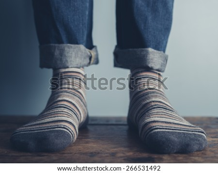 The feet of a man standing on a wooden floors wearing stripey socks - stock photo