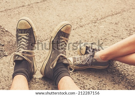 The feet of a young couple sitting in the street wearing similar shoes - stock photo