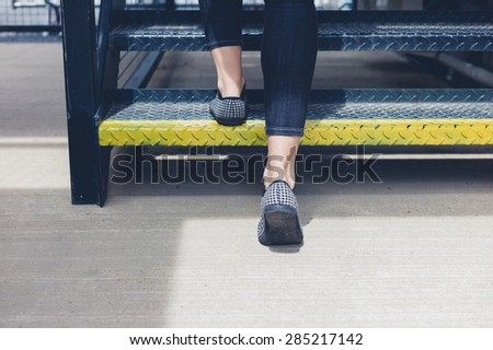 The feet of a young woman as she is walking up some metal stairs - stock photo