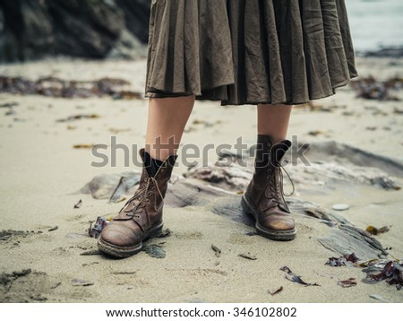 The feet of a young woman wearing hiking boots on the beach - stock photo