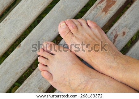 The feet of an old woman on an old wooden surface. - stock photo
