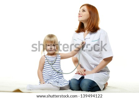 The female doctor and the small patient with a stethoscope sit on a white background. - stock photo