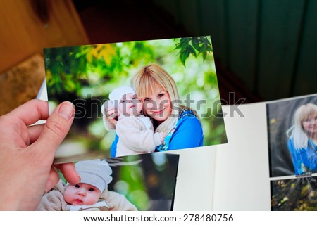 The female hand holding in hand an album with family photos - stock photo