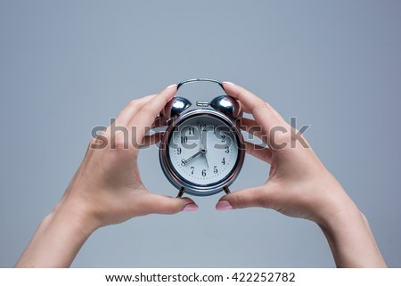 The female hands and old style alarm clock  - stock photo