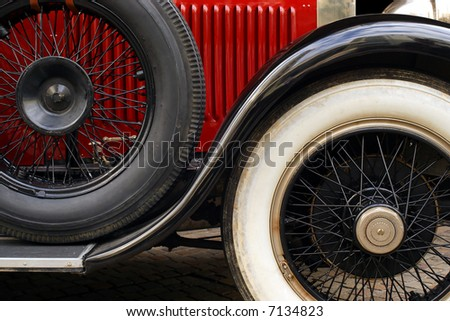 The fender and spoked wheels of an antique classic car. - stock photo