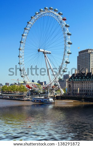 The Ferris wheel in London: The London Eye, reflected on the River Thames. - stock photo