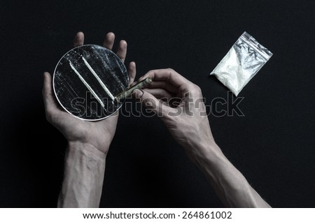 The fight against drugs and drug addiction topic: addict hand holds a mirror with strips of cocaine and drugs around her lie on a dark background, top view in the studio - stock photo