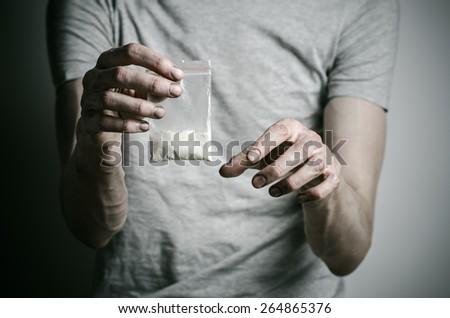 The fight against drugs and drug addiction topic: addict holding package of cocaine in a gray T-shirt on a dark background in the studio - stock photo