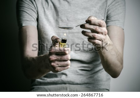 The fight against drugs and drug addiction topic: addict holding spoon lighter and heats the liquid drug in a T-shirt on a dark background - stock photo