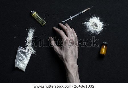 The fight against drugs and drug addiction topic: hand addict lies on a dark table and around it are drugs, a top studio