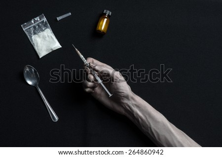 The fight against drugs and drug addiction topic: hand holding a syringe with a drug addict drugs and drugs around her lie on a dark background, top view in the studio - stock photo